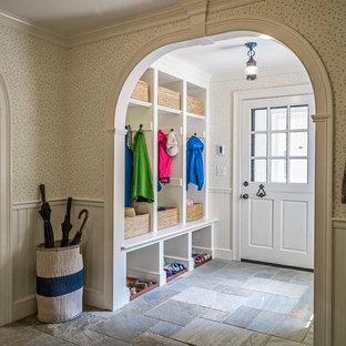 Klassisk inredning av ett stort kapprum, med flerfärgade väggar, skiffergolv, en tvådelad stalldörr och en vit dörr