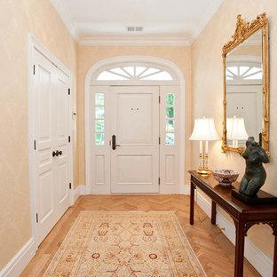 Aménagement d'un hall d'entrée classique de taille moyenne avec un mur orange, un sol en bois clair, une porte blanche et une porte simple.
