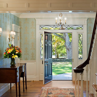 Photo of a mid-sized traditional foyer in New York with blue walls, light hardwood floors, a single front door, a white front door and beige floor.