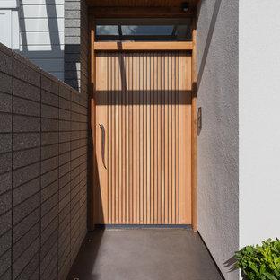 Exemple d'une grand porte d'entrée moderne avec un mur blanc, béton au sol, une porte simple et une porte en bois brun.