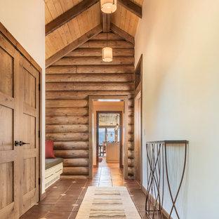 Entryway - mid-sized rustic ceramic floor and brown floor entryway idea in Denver with beige walls and a medium wood front door