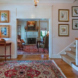 ナッシュビルの中サイズのヴィクトリアン調のおしゃれな玄関ロビー (ピンクの壁、無垢フローリング、白いドア) の写真