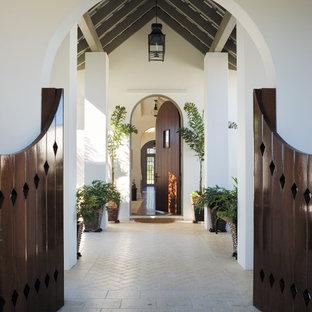 Medelhavsstil inredning av en stor farstu, med en enkeldörr, mörk trädörr, vita väggar, tegelgolv och beiget golv