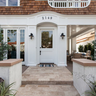 Entryway - beach style entryway idea in Orange County with a white front door