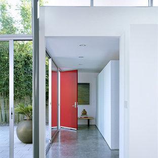 Idée de décoration pour un hall d'entrée minimaliste de taille moyenne avec béton au sol, une porte rouge, un sol gris, un mur blanc et une porte simple.