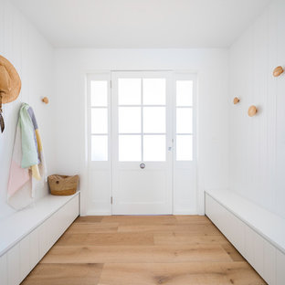 This is an example of a contemporary mudroom in Central Coast with white walls, light hardwood floors, a single front door and a white front door.