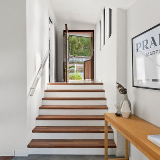 Inspiration for a contemporary front door in Sydney with white walls, a single front door, a medium wood front door and grey floor.
