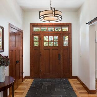 Imagen de distribuidor de estilo americano, de tamaño medio, con paredes blancas, suelo de baldosas de cerámica, puerta simple, puerta de madera oscura y suelo negro