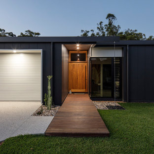 This is an example of a mid-sized contemporary front door in Sunshine Coast with a single front door and a medium wood front door.