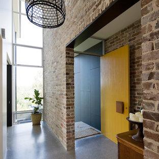 Inredning av en modern mellanstor ingång och ytterdörr, med betonggolv, en pivotdörr och en gul dörr
