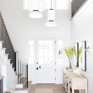 Modelo de puerta principal costera, de tamaño medio, con paredes blancas, suelo de madera clara, puerta simple, puerta blanca y suelo beige