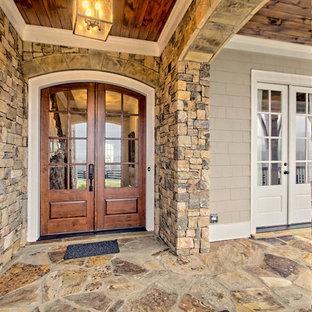 Ejemplo de puerta principal grande con paredes multicolor, suelo de pizarra, puerta doble y puerta de madera oscura