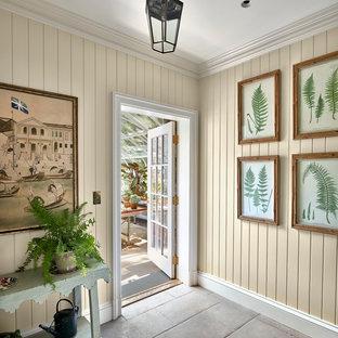 Inspiration för stora klassiska kapprum, med beige väggar, en enkeldörr, glasdörr, betonggolv och grått golv
