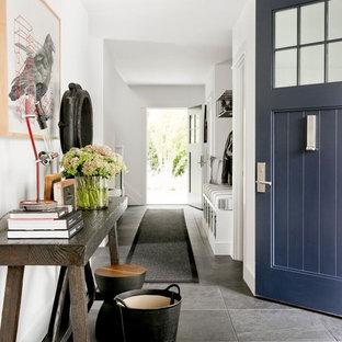Новые идеи обустройства дома: огромное фойе в стиле кантри с белыми стенами, полом из сланца, одностворчатой входной дверью, синей входной дверью и черным полом