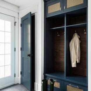 Réalisation d'une entrée champêtre de taille moyenne avec un vestiaire, un mur blanc, un sol en carrelage de porcelaine, une porte simple, une porte en verre et un sol gris.