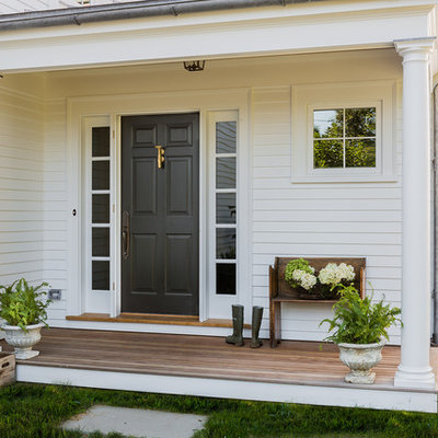 Entryway - traditional medium tone wood floor entryway idea in Boston with white walls and a black front door