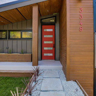 Example of a large trendy limestone floor entryway design in Vancouver with metallic walls and a red front door