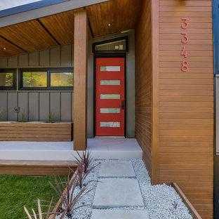 Foto på en stor funkis ingång och ytterdörr, med metallisk väggfärg, kalkstensgolv, en enkeldörr och en röd dörr