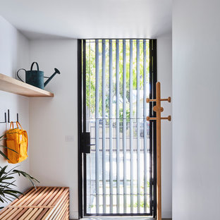 Inspiration for a contemporary mudroom in Melbourne with white walls, concrete floors, a single front door, grey floor and a glass front door.