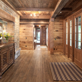 Example of a mountain style medium tone wood floor foyer design in Minneapolis with multicolored walls and a medium wood front door