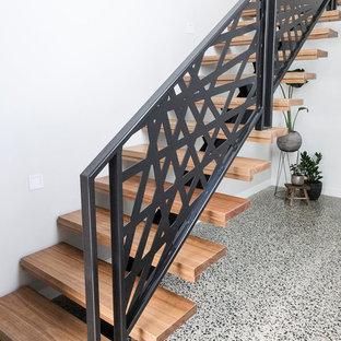 Idee per una porta d'ingresso minimalista di medie dimensioni con pareti bianche, pavimento in sughero, una porta singola, una porta in legno bruno e pavimento grigio