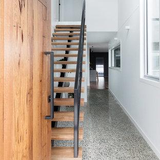Idées déco pour une porte d'entrée moderne de taille moyenne avec un mur blanc, un sol en liège, une porte simple, une porte en bois brun et un sol gris.