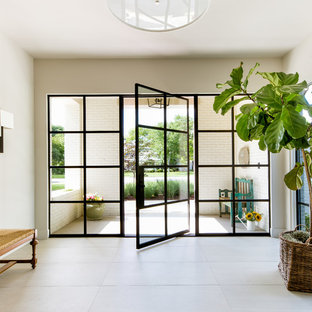 Diseño de distribuidor costero con paredes grises, puerta pivotante, puerta de vidrio y suelo gris