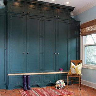 Idée de décoration pour une entrée tradition avec un vestiaire, un sol en carreau de terre cuite et un sol rouge.