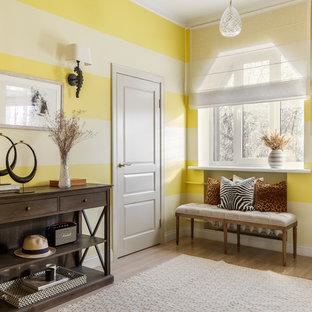 Cette image montre un vestibule bohème avec un mur jaune, un sol en bois clair et un sol beige.