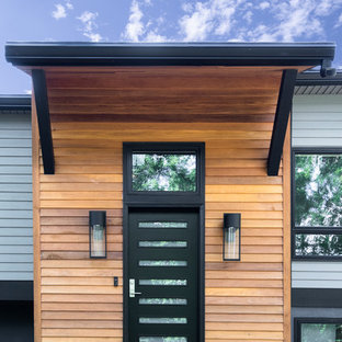 На фото: большая входная дверь в современном стиле с бетонным полом, одностворчатой входной дверью, черной входной дверью и серым полом с