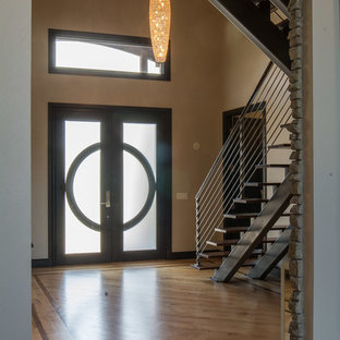 Large arts and crafts light wood floor and beige floor entryway photo in Oklahoma City with beige walls and a glass front door