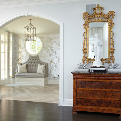 Example of a large classic light wood floor and brown floor entryway design in New York with gray walls