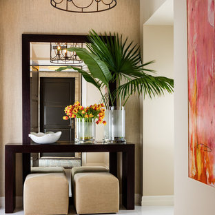マイアミの中サイズの片開きドアトロピカルスタイルのおしゃれな玄関ロビー (ベージュの壁、磁器タイルの床、グレーのドア、白い床) の写真