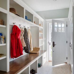ボストンの広い片開きドアトランジショナルスタイルのおしゃれなマッドルーム (青い壁、セラミックタイルの床、白いドア) の写真