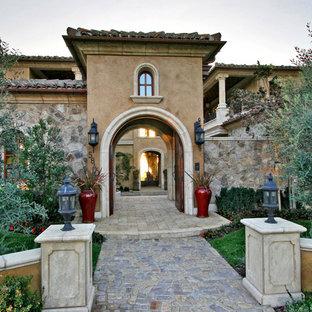 Inspiration för en mycket stor medelhavsstil ingång och ytterdörr, med en dubbeldörr, bruna väggar, tegelgolv, mellanmörk trädörr och grått golv