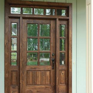 На фото: входная дверь в стиле кантри с зелеными стенами, одностворчатой входной дверью и входной дверью из темного дерева
