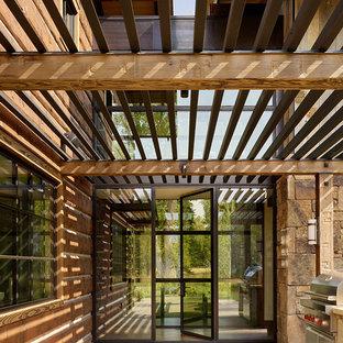 Idées déco pour une porte d'entrée montagne avec un mur marron, une porte simple et une porte en verre.