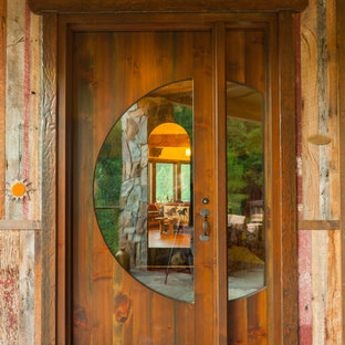 Large mountain style gray floor entryway photo in Seattle with a medium wood front door and brown walls