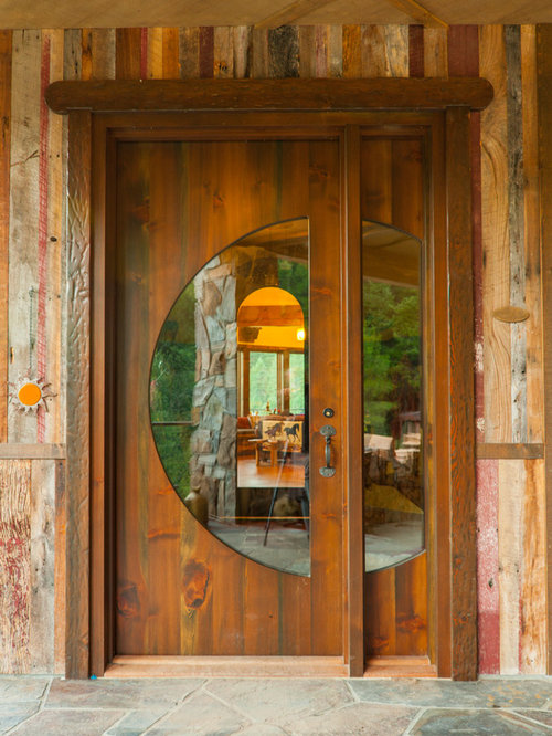 Large mountain style gray floor entryway photo in Seattle with a medium  wood front door and