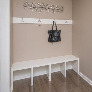 Exempel på ett litet klassiskt kapprum, med beige väggar, mörkt trägolv och brunt golv