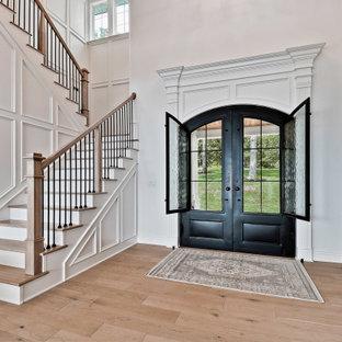 他の地域の広い両開きドアトラディショナルスタイルのおしゃれな玄関ドア (白い壁、淡色無垢フローリング、金属製ドア、ベージュの床、板張り壁) の写真