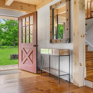 Mittelgroße Landhausstil Haustür mit weißer Wandfarbe, braunem Holzboden, Einzeltür, roter Tür und freigelegten Dachbalken in New York