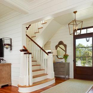 Diseño de distribuidor tropical con paredes blancas, suelo de madera en tonos medios, puerta simple y puerta de vidrio
