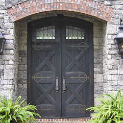 "Old World Doors - This Old World Entryway was custom designed and built by Doors By Decora for the home of a Montgomery, Alabama Attorney.  It consists of a pair of 36"" X 96"" Cross Buck Cypress Doors with V-Groove Panels and a 24"" Transom.  The transom and doors are rabbited on top so that when closed they give the appearance of a pair of 10 foot doors.  The glass in the transom is Leaded Seedy Glass and we designed and built an Iron Grill for the outside.  We used Acorn Strap Hinges and Rocky Mountain Hardware."