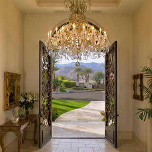 Example of a tuscan travertine floor entryway design in Los Angeles with a metal front door