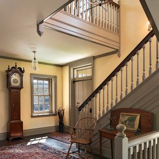 Entryway - farmhouse dark wood floor entryway idea in Philadelphia with yellow walls and a gray front door
