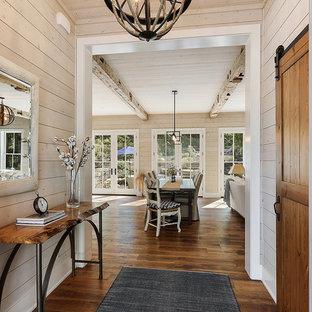 Idées déco pour une porte d'entrée bord de mer de taille moyenne avec un mur marron, un sol en bois foncé, une porte simple, une porte en bois foncé et un sol marron.