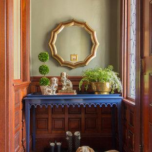 Immagine di un ingresso con vestibolo chic con pareti verdi, pavimento in legno massello medio e una porta in legno bruno