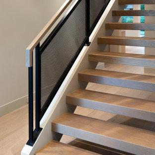 Ejemplo de distribuidor abovedado, moderno, de tamaño medio, con paredes beige, suelo de madera clara, puerta simple y suelo gris