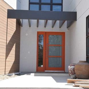 Foto de puerta principal moderna, de tamaño medio, con paredes blancas, suelo de cemento, puerta simple y puerta naranja